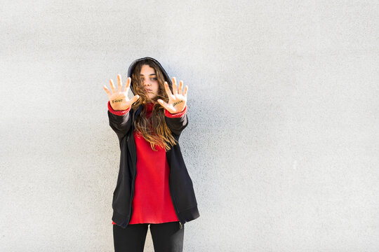 Portrait of serious teenage girl showing the words fight and sexism written on her palms