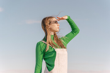 Young woman shielding eyes against the sun