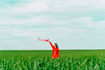 Woman wearing red dress standing  on a field holding windsock