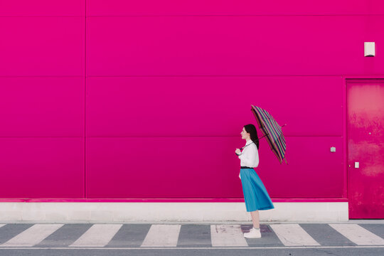 Young woman with umbrella in front of a pink wall