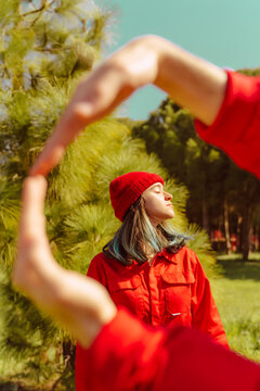 Young woman dressed in red enjoying sunlight in nature
