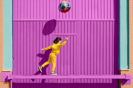 Little girl dressed in yellow balancing on bar in front of purple garage door holding balloon