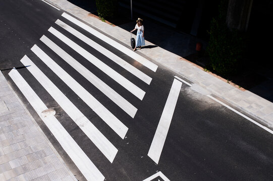 Top view of young woman with baggage crossing a street at the airport