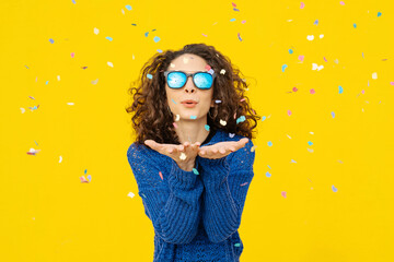 Portrait of young woman with mirrored sunglasses blowing confetti in the air in front of yellow background