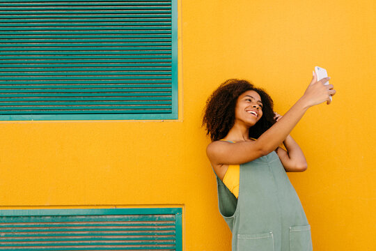 Portrait of happy young woman wearing overalls in front of yellow wall taking a selfie