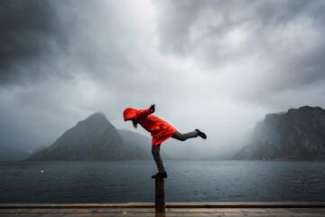Norway, Lofoten, man balancing on a pole at the coast