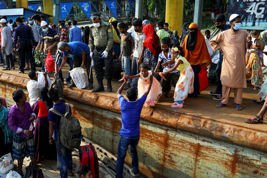 Migrant people get on board of a boat at the Sadarghat Launch Terminal, in Dhaka