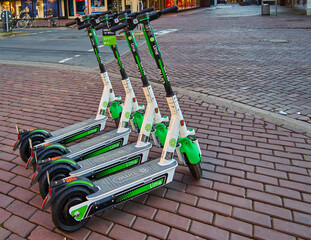 Parked e-scooters from lime rental company for rent on the sidewalk in Hannover, Germany, August 24., 2019