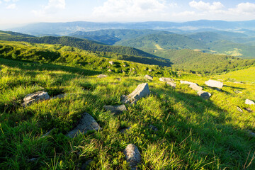 Wall Mural - row of huge rocks on a grassy hill. lovely summer scenery of Carpathian mountains. clouds on the blue sky. explore the world concept