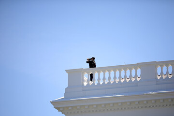 USSS Officer looks through binoculars from White House roof in Washington