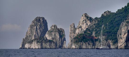 Islotes en la Isla de Capri, bahía de Nápoles, Italia con barco fondeados.