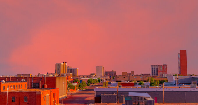 A brilliant sunset colors downtown Lubbock, Texas, including the streets and buildings.