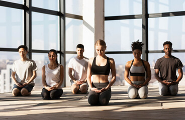 Young women and men making meditation exercises during yoga class