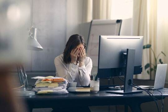 Very stressed business woman sitting in front of her computer with her hands in front of her eyes, feeling sad and depressed