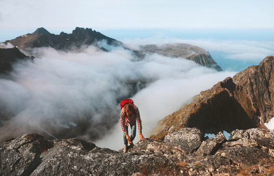 Hiker man climbing on mountain top above clouds travel hiking with backpack outdoor extreme adventure vacation active healthy lifestyle trekking in Norway