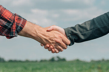 Mortgage loan officer and farmer shaking hands upon reaching an agreement