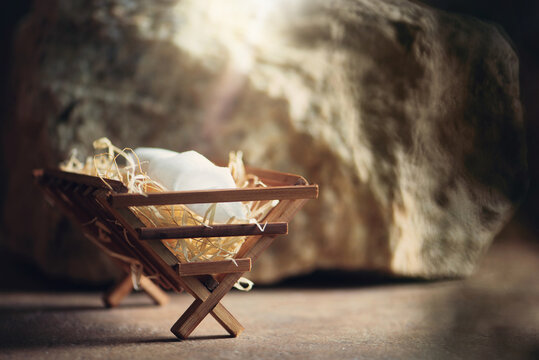Christian Christmas concept. Birth of Jesus Christ. Wooden manger in cave background. Banner, copy space. Nativity scene symbol. Jesus is reason for season. Salvation, Messiah, Emmanuel, God with us.
