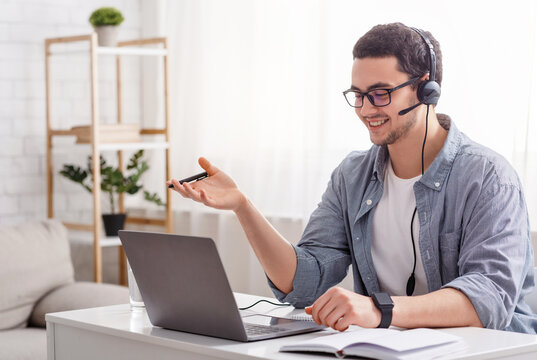 Online teacher and work from home. Guy in glasses and headset talking with student