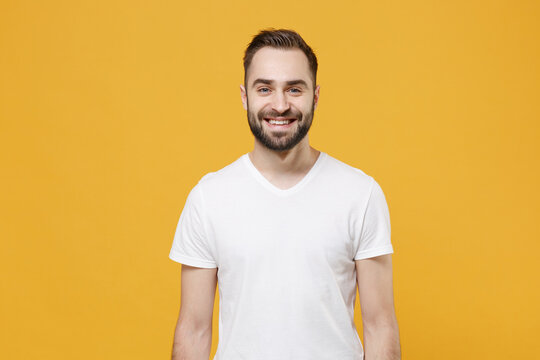Smiling handsome young bearded man guy in white casual t-shirt posing isolated on yellow wall background studio portrait. People sincere emotions lifestyle concept. Mock up copy space. Looking camera.