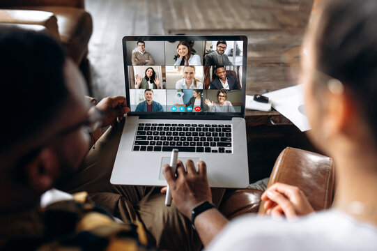 Online business meeting. Business colleagues communicate by a video conference using a laptop, solving and analyzing business affairs. On a laptop screen, participants of a video conference