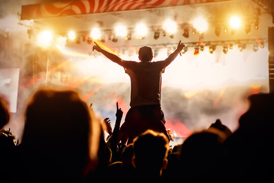 Man with raised hands opposite stage light. Night club party.