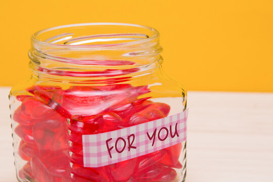 jar with hearts on the table, pink sticker with the inscription for you on the jar, yellow background, give love concept, valentines day, mothers day postcard