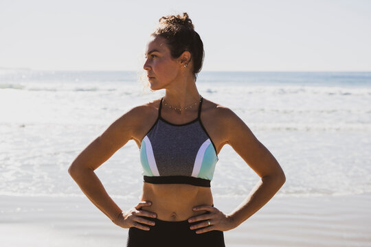 Attractive curly hair athletic young woman wearing sportswear at the beach with hands on waist on a sunny day and blue sky.