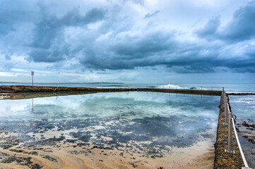 Empty rock pool with clear water and overcast sky