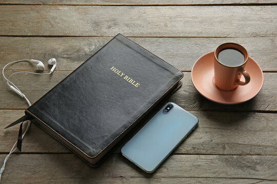 Holy Bible, tea, mobile phone and earphones on wooden background