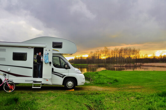 RV camper and woman in camping on sunset, family vacation travel, holiday trip in motorhome