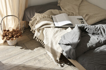 Unmade bed with book at sunlight