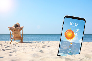 Young woman relaxing in deck chair on sandy beach and smartphone with open weather forecast app