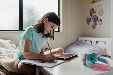 Young preteen girl alone in her bedroom using her tablet computer for remote online learning at home and writing in her school work book