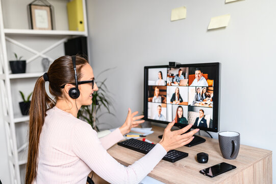 Online meeting, remote work. Young business woman with glasses using app on PC for video communication with many people together, she has headset for talking online with employees. Back view