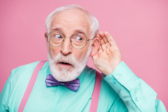 Closeup photo of attractive grandpa hand near ear listen rumors focused chatterbox bad person wear specs mint shirt suspenders violet bow tie isolated pink pastel color background
