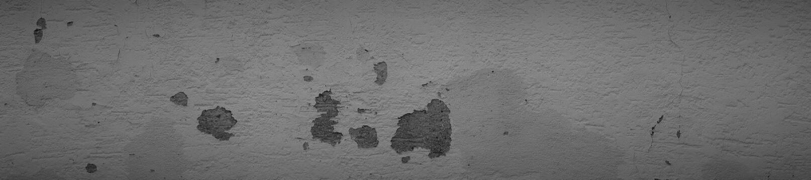Dark rough cracked house wall texture. Cracked concrete wall in dark gray in widescreen format.