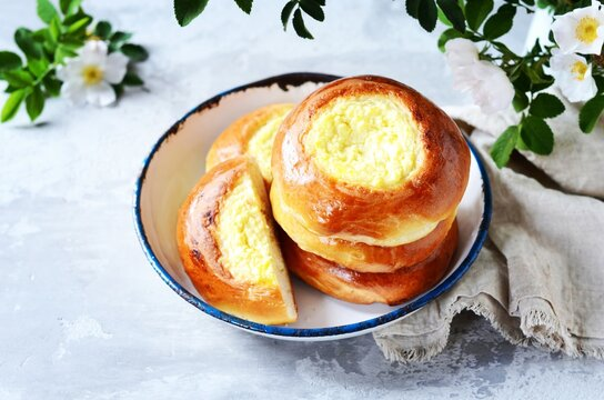 Homemade buns with cottage cheese (cheesecakes) in a dish on a gray background, Russian cuisine