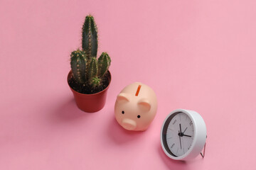 Time to invest. White clock and piggy bank, cactus on pink pastel background. Minimalistic studio...