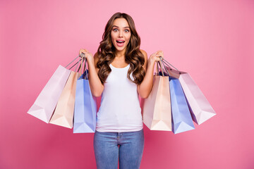 Photo of attractive lady long perfect curly hair amazing mood hold many packs addicted shopper sale prices wear white casual singlet jeans isolated pink color background