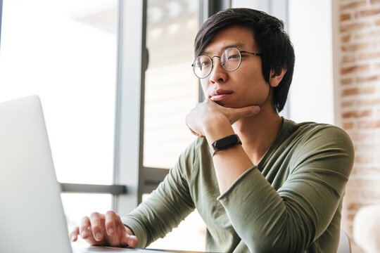 Image of handsome young asian man using laptop in apartment