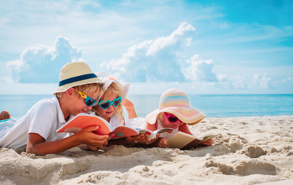 happy kids -boy and girls- read books on beach, summer reading on vacation