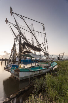 Well worn shrimping boat docked on a shore in the bayou of southern Louisiana