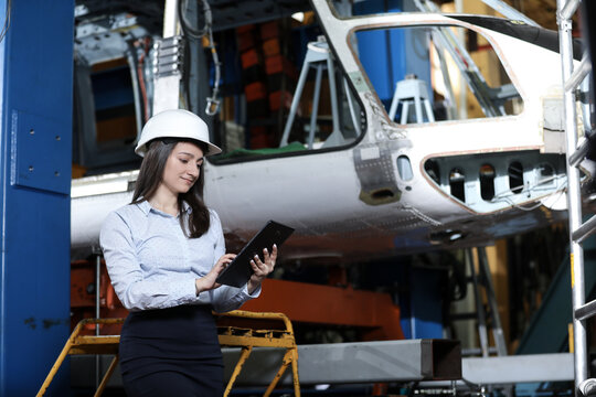 Portrait of a solid businesswoman holding tablet , controlling work process in a airplane manufactory. Office worker.