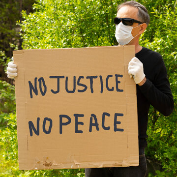 """A white man holds a sign that says """"There is no justice, no peace"""" in protest against the murder of"""