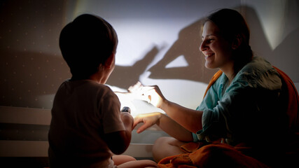 Portrait of smiling young mother and little boy playing with flashlight and shadows on wall at night