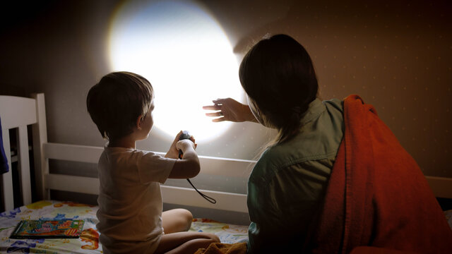 Little boy and young mother showing shadow theater on wall in bedroom at night