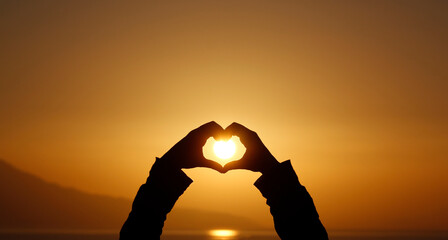Woman making heart with hands in sunset. Love symbol in sunny summer day.