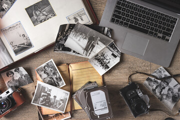 Old family photos and album on wooden background. Vintage pictures, camera, notepad and modern notebook composition. Flat lay.