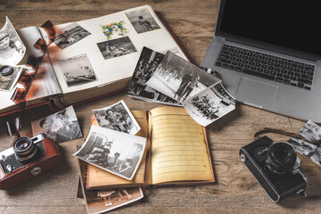 Old family photos and album on wooden background. Vintage pictures, camera, notepad and modern notebook composition. Wall mural
