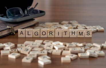 algorithms concept represented by wooden letter tiles on a wooden table with glasses and a book